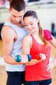 Two smiling people working out with dumbbells — Stockfoto