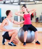 Entrenador masculino con mujer haciendo abdominales en la bola — Foto de Stock