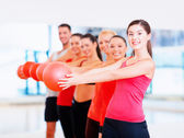 Group of smiling people working out with ball — Stok fotoğraf