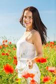 Sonriente mujer joven en campo de amapolas — Foto de Stock