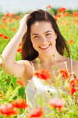 Smiling young woman on poppy field — Stockfoto