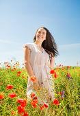 Mulher jovem sorridente no campo de papoulas — Fotografia Stock