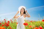 ケシ畑に麦わら帽子の若い女性を笑顔 — ストック写真