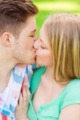 Smiling couple kissing and hugging in park — Stock Photo