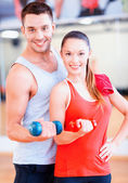 Two smiling people working out with dumbbells — Stok fotoğraf