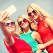 Smiling girls taking photo with smartphone camera — Stock Photo