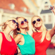 Three beautiful girls taking picture in the city — Stock Photo #50492455