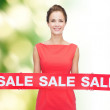 Smiling young woman in dress with red sale sign — Stock Photo #50495121