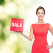 Smiling young woman in dress with red sale sign — Stock Photo #50495177