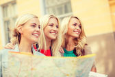 Beautiful blonde women with map in the city — Stock Photo