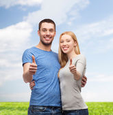 Smiling couple showing thumbs up — Stok fotoğraf