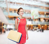 Smiling woman with shopping bags and plastic card — Stok fotoğraf