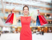 Laughing elegant woman in dress with shopping bags — Stok fotoğraf