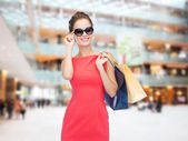 Smiling elegant woman in dress with shopping bags — Stok fotoğraf