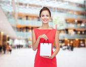 Smiling elegant woman in dress with shopping bag — Stok fotoğraf