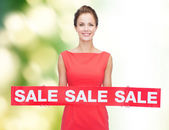 Smiling young woman in dress with red sale sign — Stok fotoğraf