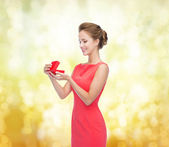 Smiling young woman in red dress with gift box — Stok fotoğraf