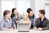 Estudantes com laptop na escola a sorrir — Fotografia Stock