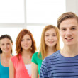 Smiling students with teenage boy in front — Stock Photo #50544371