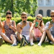 Smiling friends with smartphones sitting on grass — Stock Photo #50544641