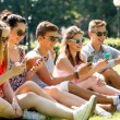 Smiling friends with smartphones sitting on grass — Stock Photo #50544681