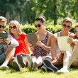 Smiling friends with tablet pc computers in park — Stock Photo #50545537
