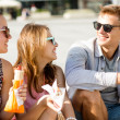 Group of smiling friends sitting on city square — Stock Photo