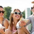 Group of smiling friends sitting on city square — Stock Photo #50546789