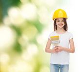 Smiling little girl in helmet with paint brush — Stock Photo