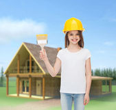 Smiling little girl in helmet with paint brush — Stok fotoğraf