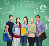 Group of smiling students with folders and bags — Stock Photo