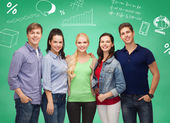 Group of smiling students over green board — Stock Photo