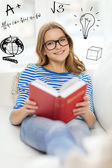 Smiling teenage girl reading book on couch — Stock Photo