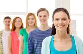 Estudiantes sonrientes con adolescente en frente — Foto de Stock