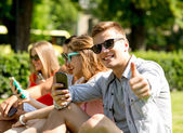 Smiling man with smartphone showing thumbs up — Stock Photo