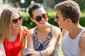 Smiling friends with smartphone sitting in park — Foto Stock