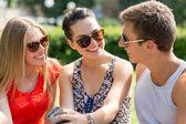 Souriant amis smartphone assis dans un parc — Photo