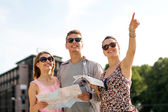Smiling friends with map and city guide outdoors — Stock Photo
