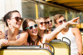 Group of smiling friends traveling by tour bus — Stockfoto