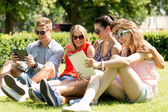 Smiling friends with tablet pc computers in park — Stock Photo