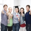 Group of students with diploma showing thumbs up — Stock Photo #50735725