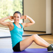 Smiling woman doing exercises on mat in gym — Stock Photo #50739231