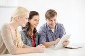 Lachende studenten met tablet pc-computer op school — Stockfoto