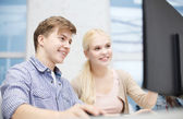 Smiling teenage boy and girl in computer class — Stock Photo