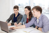 Three smiling students with laptop and notebooks — Stock Photo