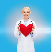 Smiling female doctor with heart and stethoscope — Stock Photo