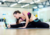 Smiling young woman stretching on mat in gym — Stock Photo