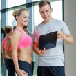 Smiling young woman with personal trainer in gym — Stock Photo #50740697