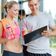 Smiling young woman with personal trainer in gym — Stock Photo #50741027