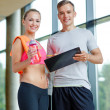 Smiling young woman with personal trainer in gym — Stock Photo #50741263